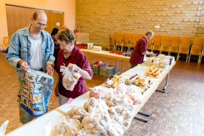 Freiwillige verteilen die Lebensmittel an die Kunden